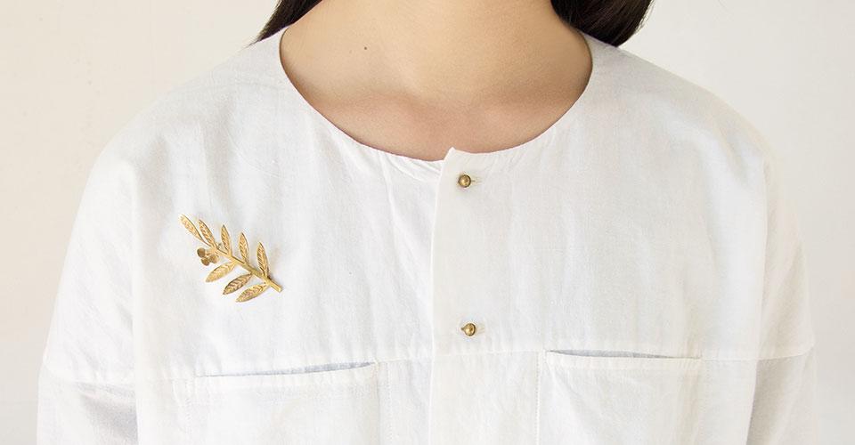 白いシャツに真鍮ブローチを挿して